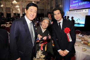 15年の報知映画賞表彰式で樹木希林さん、本木雅弘(右)とともに笑顔を浮かべる岡田裕介さん
