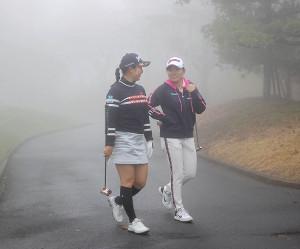 濃霧のため競技が一時中断され、スタート前の小祝さくら(左)と勝みなみが練習を中止してクラブハウスへ戻る