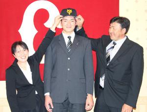 母恵さん(左)と父貢さん(右)に囲まれ照れ笑いを浮かべる札幌大谷高・阿部
