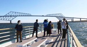 屋形船のデッキに出て東京ゲートブリッジを眺める人たち