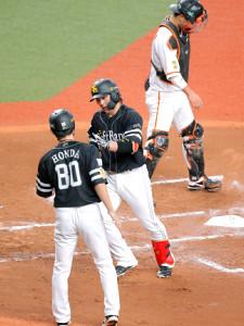 2回1死、中越えにソロ本塁打を放った甲斐拓也(右)は本多コーチ(80番)に迎えられる(右上は捕手の大城卓三)