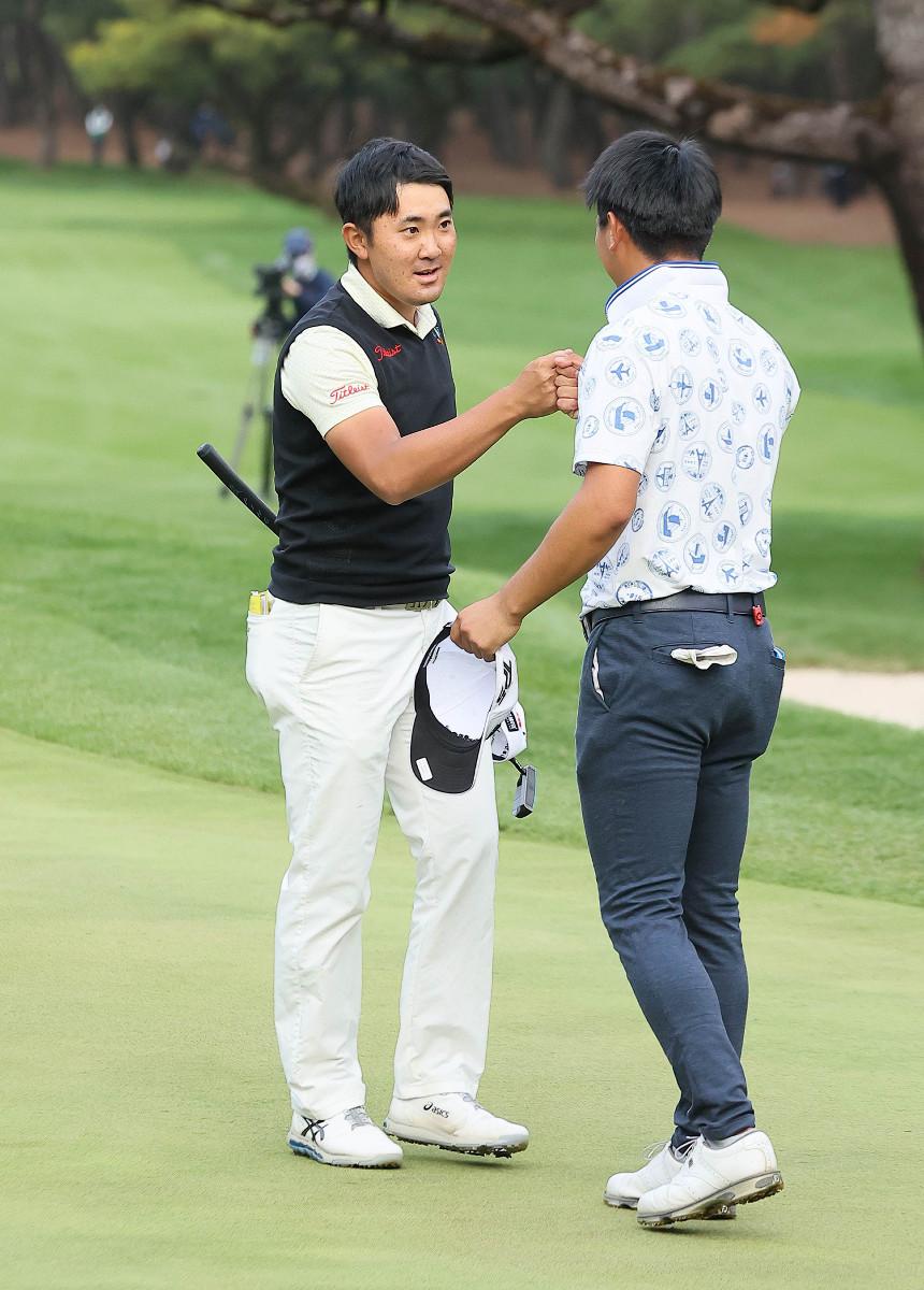 プレーオフ4ホールの末に優勝を決め、石坂友宏(右)と健闘を称え合う金谷拓実(カメラ・馬場 秀則)