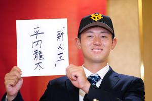 「新人王」と記した色紙を手にポーズをとる亜大・平内(カメラ・矢口 亨)
