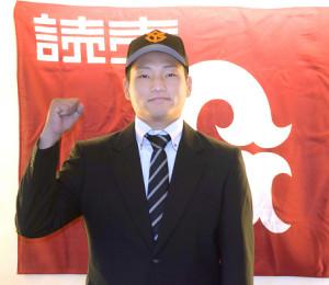 仮契約を終え、巨人のキャップをかぶって気合を見せる育成ドラフト10位の山崎友輔