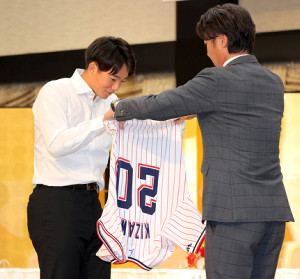ヤクルト新入団選手発表で、高津臣吾監督からユニホームを手渡された木沢尚文(左)