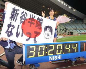 日本新を表示する計時板を前に笑顔でポーズする新谷