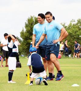 今年6月、子どもたちと一緒に汗を流して笑顔を見せた五郎丸(右)