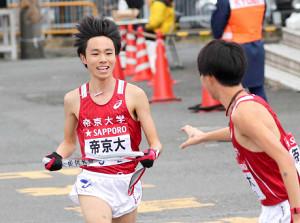 前回大会で、2区の帝京大・星岳(左)が3区の遠藤大地にタスキを渡す