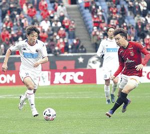 19日の浦和戦でドリブル突破を図る、吉原氏が来季の活躍を期待する札幌MF金子(左)