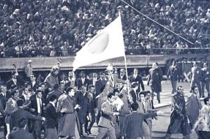 64年東京五輪の閉会式で外国人選手に担がれて入場する福井旗手