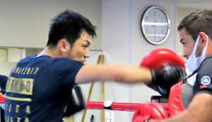 カルロス・トレーナー相手にミット打ちをする村田(左)