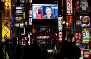 緊急事態宣言発令の会見に臨む菅首相の映像が流れる繁華街(ロイター)