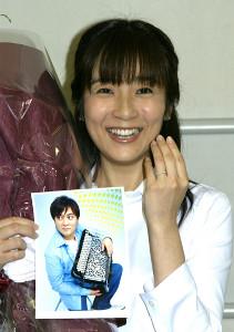 桑山哲也さんの写真を手に、婚約指輪を見せる女優の藤田朋子(2005年4月4日撮影)