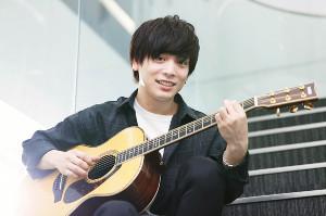 「ドライフラワー」を制作したというギターを手に優しい笑顔を浮かべる優里(カメラ・山崎 賢人)
