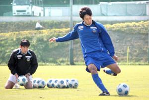 川崎の監督時代、シュート練習を行う関塚氏(左)と憲剛(09年10月21日)