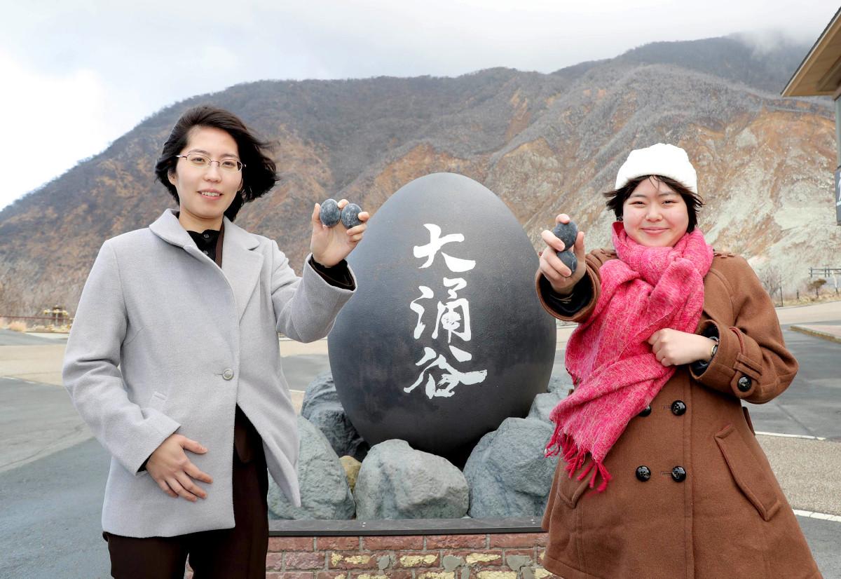 強風の大涌谷で名物「黒たまご」を手に笑顔の里見香奈女流名人(左)と加藤桃子女流三段(カメラ・関口 俊明)