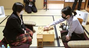 昼食後に対局が再開し、40手目を指す里見香奈女流名人(右)。左は挑戦者の加藤桃子女流三段