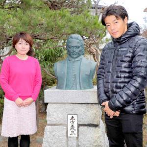 土方歳三の胸像をはさんで記念撮影する羽根田(右)と土方愛さん