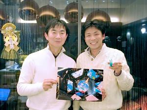"""選抜試験の""""同期""""だった宇宙飛行士の油井亀美也さん(左)が国際宇宙ステーション(ISS)内で撮影した写真とその時に使った折り鶴を手にする内山崇さん"""