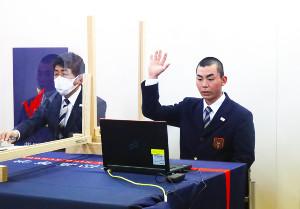 挙手をしてくじを引く柴田の遠藤主将(右)と見守る平塚監督