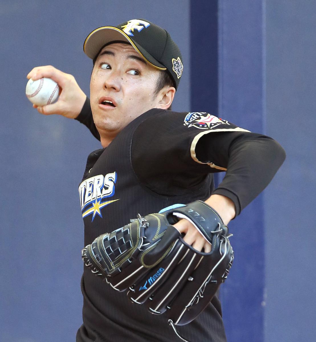 ブルペンで投球練習する日本ハム・斎藤
