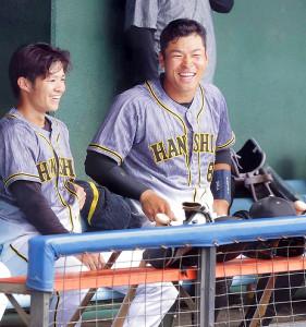 練習試合中、ベンチで中野(左)と談笑する佐藤輝(カメラ・渡辺 了文)