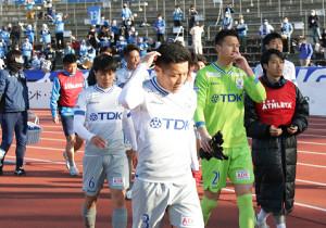 試合後、悔しさをにじませながらサポーターにあいさつする秋田イレブン