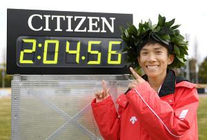 2時間4分56秒の日本新記録のタイム表示板を前に笑顔を見せる鈴木健吾