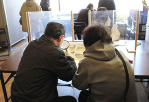 仙台市若林区文化センターで行われた返却会に写真を探しに来た夫婦(おもいでかえる提供)