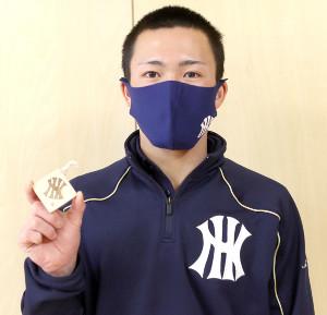 八戸高等支援学校の生徒たちから贈られたキーホルダーを手にする八戸西・宮崎主将。裏側には「一球入魂」の文字