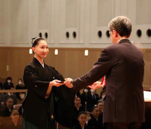 宝塚音楽学校卒業式で小林公一校長から卒業証書を受け取る第107期生の首席・西村あみさん(宝塚音楽学校提供)
