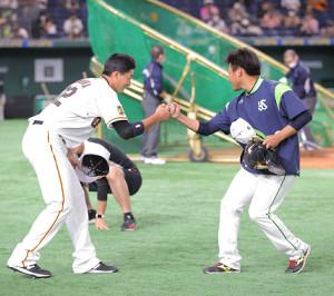 田口麗斗(右)とグータッチをする広岡大志