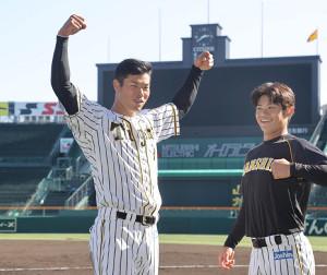甲子園球場で初めて練習を行い、ポーズを決める佐藤輝(右は中野=カメラ・岩崎 龍一)