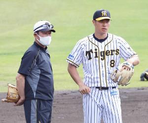 佐藤輝(右)と話をする川相臨時コーチ
