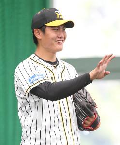 投球練習の合間に笑顔を見せる西純矢