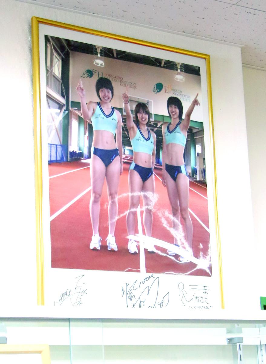 恵庭市のインドアスタジアムのホールに飾られている北海道ハイテクAC「3人娘」の写真