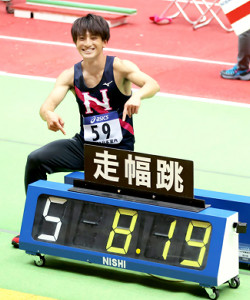 男子走り幅跳びで室内日本新記録を更新した橋岡は、ボードの前で笑顔を見せる