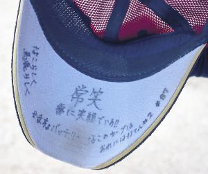 阿部の帽子のつば裏側に書かれた「常笑」