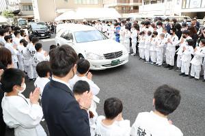 古賀さんのひつぎを乗せた車は、古賀塾の子どもたちに見送られる(代表撮影)