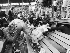 73年10月22日、甲子園球場で行われた最終戦で巨人がV9を決めたが、怒りのあまりグラウンドになだれ込んだ阪神ファンは、ベンチの王(中央右)ら巨人ナインを襲撃した