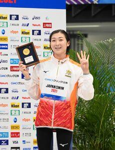 女子50メートル自由形で優勝し、メダルを掲げ笑顔の池江璃花子。今大会4冠を達成した