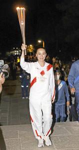 東大寺南大門でトーチを掲げ、笑顔を見せる映画監督の河瀬直美(代表撮影)
