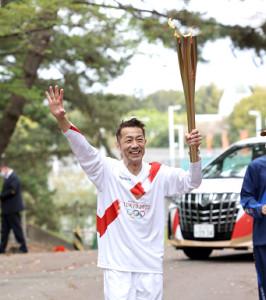 聖火リレーに参加し、笑顔で手を振る森脇健児さん(代表撮影)