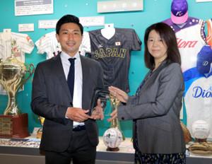 全日本女子野球連盟の山田博子会長(右)から表彰された、東都大学準硬式野球連盟の杉山智広理事長(カメラ・軍司 敦史)