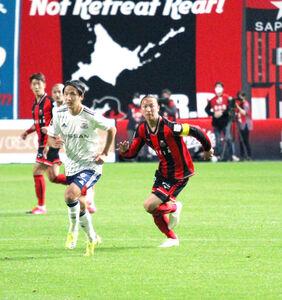 ボールの行方を見ながら走る札幌MF荒野拓馬(右)