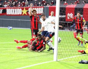 横浜M戦の後半2分、倒れながらゴールを決める札幌FWアンデルソンロペス(手前左)