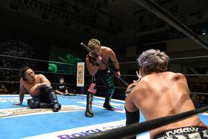 リング上で「棒」にキスをするYOSHI―HASHI(中央)を見つめるKENTA(新日本プロレス提供)