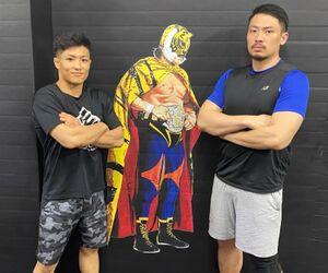 「佐山道場」の初代タイガーマスク壁画をバックにポーズを決める平沼ヤマト(左)と佐山聖斗さん