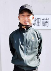 鉄色の厩舎ジャンパーを着る畑端省吾調教師