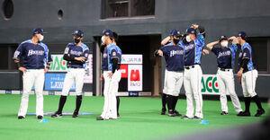 1日、マスク姿で試合前にベンチ前で準備運動する日本ハムナイン